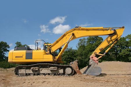 idle: Yellow digger standing idle on a construction site, with trees and a blue sky to the rear. Stock Photo