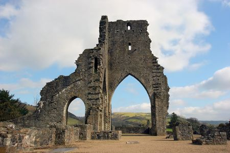 walling: Talley Abbey ruins in Wales, United Kingdom, with rural countryside beyond the main arch. Set against a pale blue sky with clouds. Stock Photo