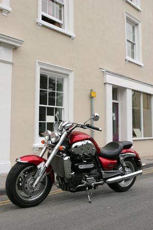 holgaz�n: Nueva brit�nico moto en met�lico de color rojo y cromo aparcados hasta en su lado de pie.