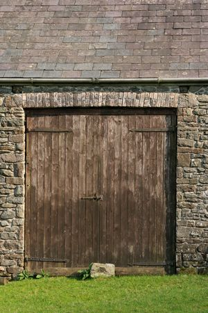 Old wooden doors on a stone barn with slate rook. Grass to the foreground. photo