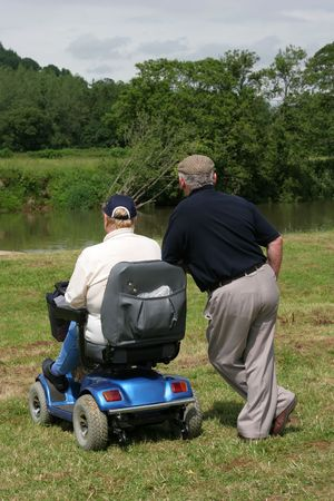 Two elderly men, one sitting on an electric  mobility scooter and one standing with both looking at a river bank in rural countryside. Rear view. photo