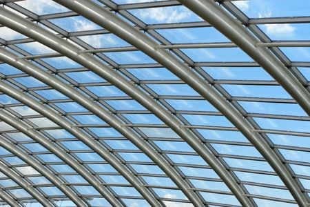 joists: Silver metal curved roof joists in a conservatory with glass panes in between and a blue sky and clouds beyond.