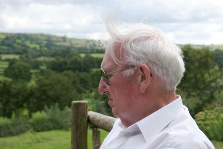 windswept: Face of an elderly man looking depressed, wearing glasses with windswept white hair.