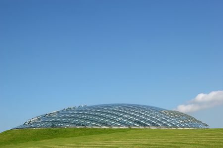 Futuristic conservatory bio sphere made of glass panels and set into a grass hillside with a clear blue sky to the rear. photo