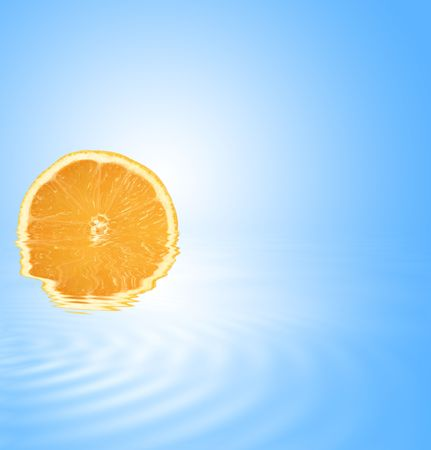 Abstract of an orange slice partially submerged in gently rippled blue water with reflection and set against a sky blue background with white glow. photo