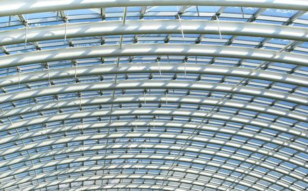 joists: Curved reinforced steel roof joists in a conservatory roof, with glass panes in between and blue sky beyond.