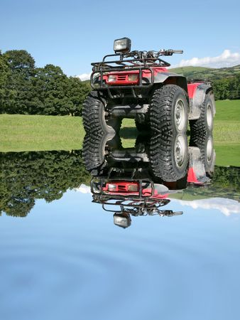 four wheel: Red and black four wheel drive quad bike, with reflection in rippled water, standing on the grass and partially submerged in the water. Rural countryside and a blue sky to the rear. Stock Photo