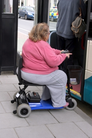 Overweight disabled female on an electric three wheeler mobility scooter waiting in line to get onto a bus Stock Photo