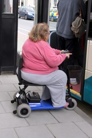 donne obese: Sovrappeso disabili femminile su un tre ruote elettrico mobilità scooter attesa in linea per arrivare su un autobus