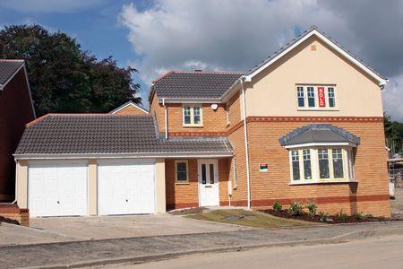 Nueva casa de ladrillo separados con un doble garaje con signos para la venta.