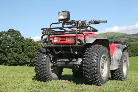 Red and black four wheel drive quad bike standing on the grass in a field in summer with rural countryside and a blue sky to the rear photo