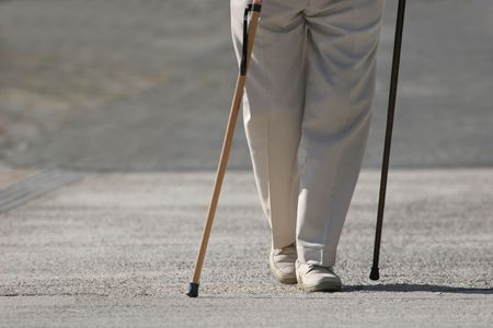 Piernas de un varón mayor que camina en un pavimento con dos palillos que caminan. Foto de archivo