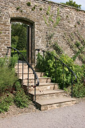handrails: Ancient garden stairway with metal handrails, set within an old stone wall and leading to a garden beyond.  Flowers and shrubs either side of the steps. Stock Photo
