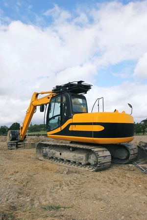 idle: Rear view of a yellow industrial digger standing idle on rough ground.