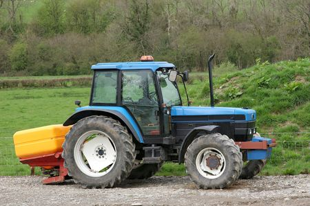 idle: Blue tractor standing idle towing a yellow plastic fertiliser spreader. Rural farmland to the rear.