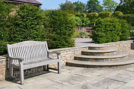 walling: Outdoor garden tiled patio area, with an old wooden oak bench, curved steps to the side and shrubs to the rear.