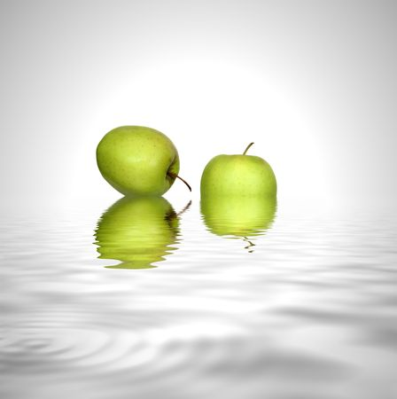 grey water: Abstract of two green apples with reflection in silver grey water, set against a silver white background.