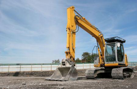 holgaz�n: Industrial excavadora amarilla permanente de inactividad en una obra de construcci�n con un cielo azul en la parte posterior.  Foto de archivo