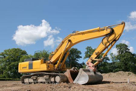 holgaz�n: Amarillo excavadora de inactividad permanente en una obra, con �rboles y un cielo azul para la parte posterior.
