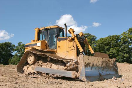 holgaz�n: Amarillo excavadora permanente de inactividad aproximada a la tierra con �rboles y un cielo azul en la parte posterior.