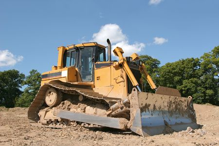 Yellow bulldozer standing idle on rough earth with trees and a blue sky to the rear. photo
