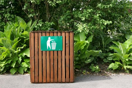 public waste: Slatted wooden litter bin with a green and white sign standing on a pathway with shrubs to the rear. Stock Photo