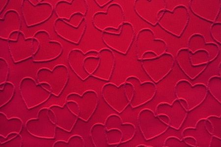 linked: Red double linked hearts embossed on fabric. Stock Photo