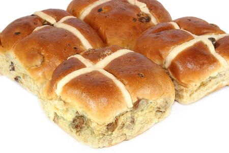 sultanas: Fresh hot cross buns against a white background. Stock Photo