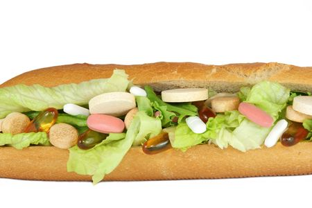 Vitamin tablets in a french bread salad roll , set against a white background.