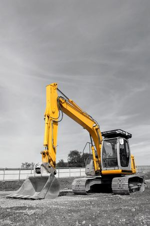 Industrial yellow digger with excavator bucket standing idle on a building site. Desuaturated with only the metal on the vehicle saturated.