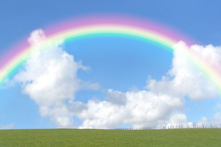Rural landscape with a green field set against a blue sky with a rainbow arc and cumulus clouds.