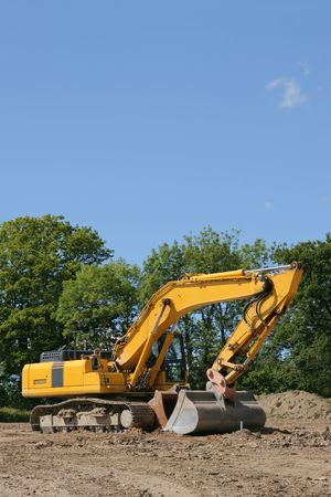 idle: Yellow digger standing idle on a building construction site, with trees and a blue sky to the rear. Stock Photo