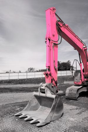 hardcore: Steel excavator bucket on a pink industrial digger, standing idle on hardcore. Desaturated with only the digger in color. Stock Photo