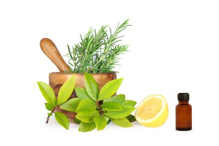 aromatherapy oils: Fresh herb selection of rosemary, bay leaves and half a lemon and an essential oil brown glass aromatherapy bottle, with an olive wood pestle and mortar. Over white background.