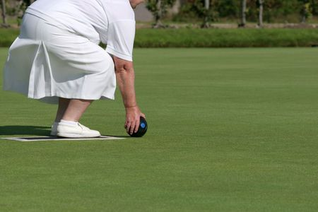 Lower body of an elderly female wearing white clothing and holding a lawn bowling ball about to bowl.