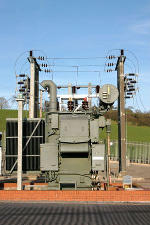 sub station: Electricity sub station set in rural countryside with a blue sky to the rear. Stock Photo