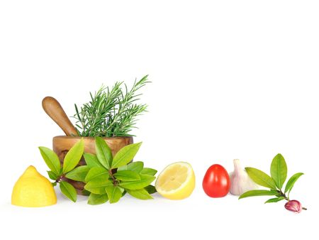 Fresh herb leaf selection of rosemary and bay with two lemon halves, a tomato and garlic clove and bulb, with an olive wood pestle and mortar to the rear. Over white background. photo