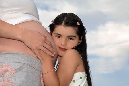 mother to be: Donna incinta che tengono le mani di una giovane ragazza premendo il viso contro il nudo ventre della madre di essere.  Archivio Fotografico