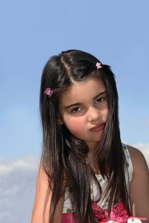 haired: Face of a young little girl with dark hair looking serious. Set against a blue sky with clouds.