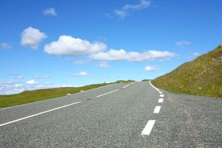 grass verge: Strada asfaltata nel paesaggio rurale con erba banchine o IDE e cala contro un cielo blu con nuvole.  Archivio Fotografico
