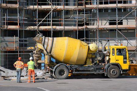 mezclador: Cami�n mezclador de cemento amarillo aparcado en fornt de un nuevo edificio en construcci�n, con andamios en la posici�n. Dos obreros de pie a la izquierda, vista posterior.
