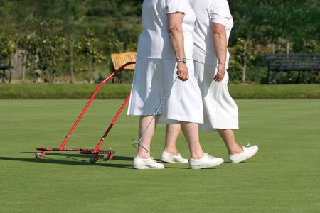 gatherer: Two elderly females in white bowling clothes walking together on a green lawn, one of the females pulling a red metal ball gatherer.