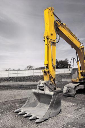 holgaz�n: Industrial con la cuchara excavadora, de pie sobre inactivo graves. Desaturated s�lo con el amarillo de la excavadora en color.