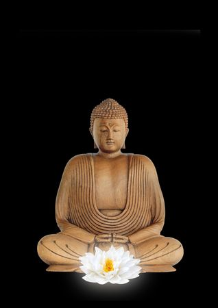 Buddha smiling, with eyes closed in prayer with a glowing white lotus lily flower in the foreground, over black background.