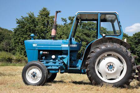 holgaz�n: Antiguo azul y blanco permanente de inactividad tractor en un campo en el verano con �rboles de la parte trasera.