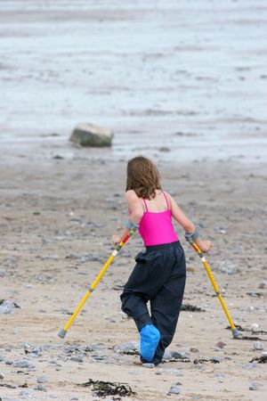 crutch: Young girl on crutches on a beach with a blue plastic bag on one foot protecting a plaster cast.