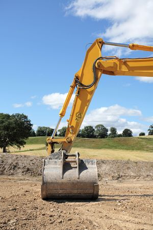 idle: Industrial metal digger hydraulic arm and bucket standing idle on rough earth with rural countryside and a blue sky and clouds to the rear. Stock Photo