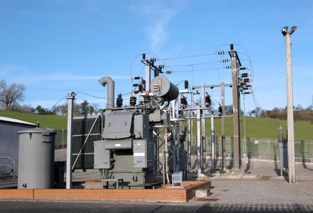 substation: Electric sub power station in rural countryside with a blue sky to the rear.