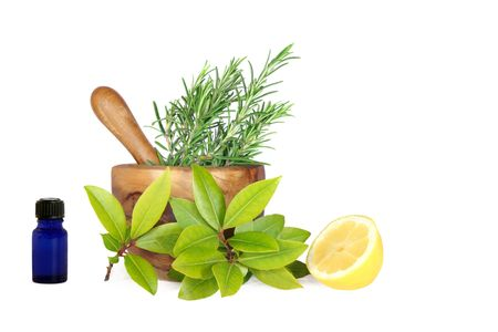 Fresh herb selection of rosemary, bay leaves and half a lemon with essential oil blue glass aromatherapy bottle and an olive wood pestle and mortar to the rear, over white background. Stock Photo