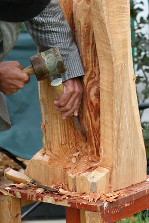 chisel: Hands of an elderly man, carving a wood sculpture with a chisel and mallet.